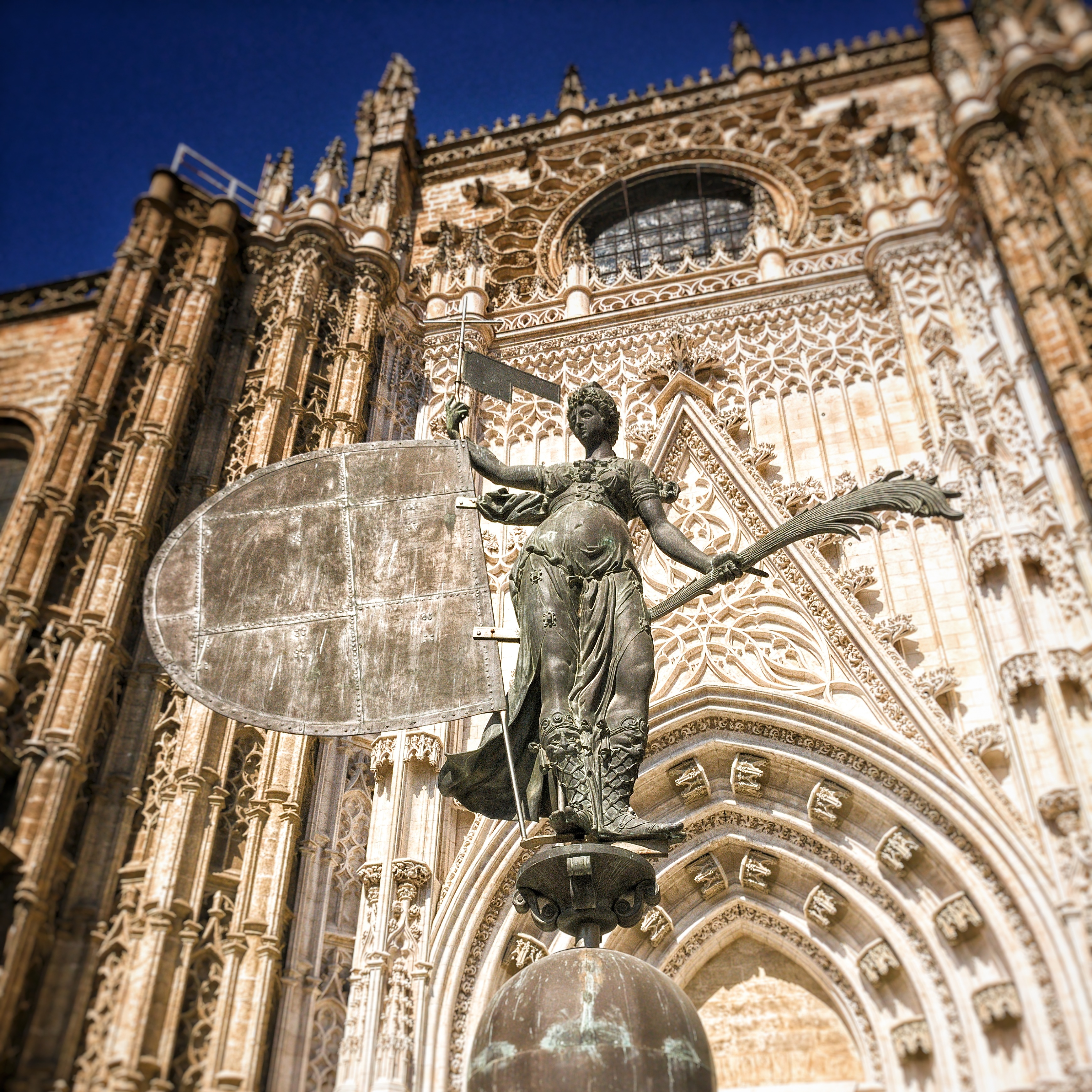 A picture of the replica of the statue on top of the Giralda in front of the entrance of the Cathedral of Sevilla.